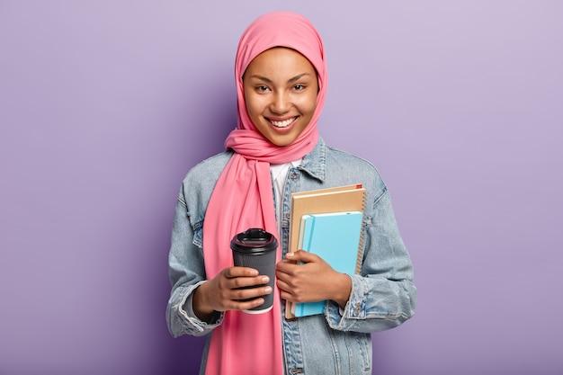 Fröhliche muslimische frau in rosa hijab, jeansmantel, trägt taschenbuch