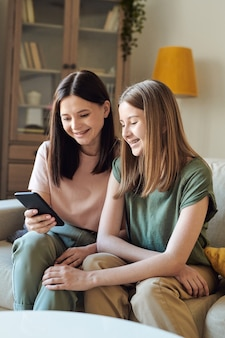 Fröhliche mutter, die auf sofa sitzt und smartphone benutzt, während lustiges video mit tochter schaut