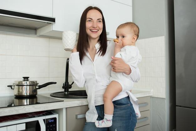 Fröhliche mutter, die in der küche steht, morgenkaffee trinkt und baby hält