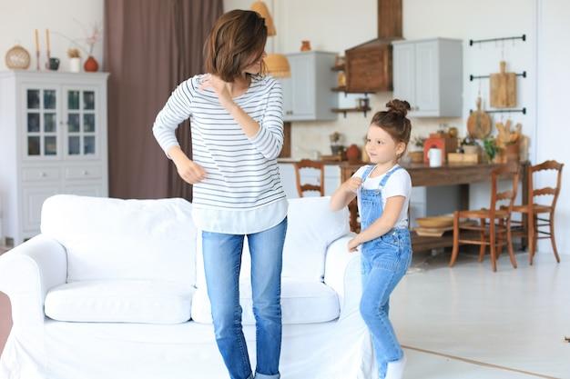 Fröhliche mutter mit kleiner tochter, die zu hause zum lieblingslied im wohnzimmer tanzt.