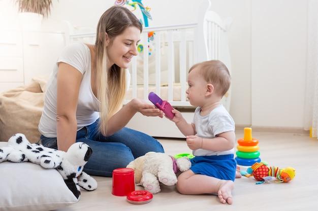 Fröhliche mutter und ihr baby auf dem boden spielen mit spielzeug Premium Fotos