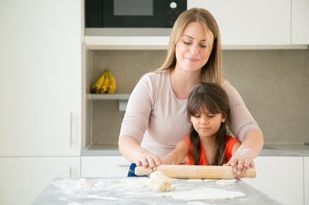 Fröhliche mutter und ihr mädchen kochen zusammen und rollen teig auf küchentisch mit mehlpulver.
