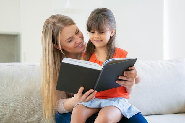 Fröhliche mutter und ihr schwarzhaariges mädchen lesen gemeinsam zu hause ein buch.