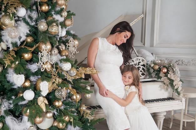 Fröhliche mutter und ihr süßes tochtermädchen mit einem weißen klavier und geschmücktem weihnachtsbaum mit geschenken, die spaß haben und im klassischen luxus-neujahrs-interieur umarmen.