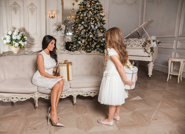 Fröhliche mutter und ihr süßes tochtermädchen tauschen geschenke im weißen klassischen interieur vor dem hintergrund eines klaviers und eines geschmückten weihnachtsbaumes aus.