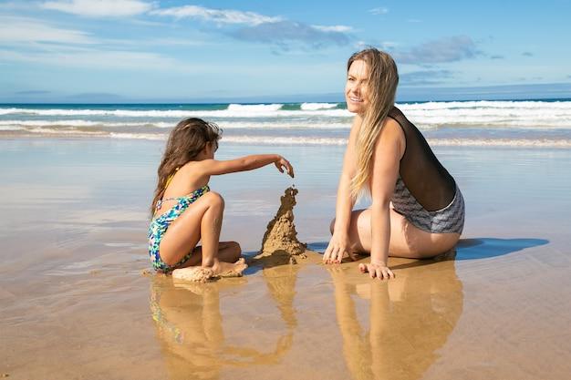 Fröhliche mutter und kleine tochter bauen sandburg am strand, sitzen auf nassem sand und genießen urlaub auf see