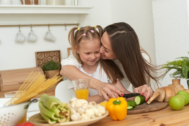 Fröhliche mutter und kleine tochter bereiten in der küche zusammen salat zu und haben spaß. das mädchen küsst ihre mutter zu hause.