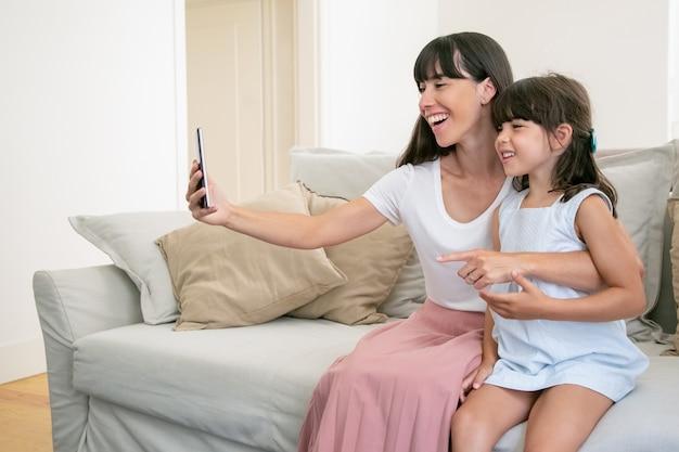 Fröhliche mutter und kleine tochter, die telefon für videoanruf verwenden, während sie zusammen auf sofa zu hause sitzen