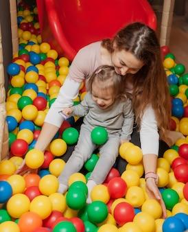 Fröhliche mutter und kleine tochter spielen im pool mit bunten bällen im kinderunterhaltungszentrum. familienurlaub