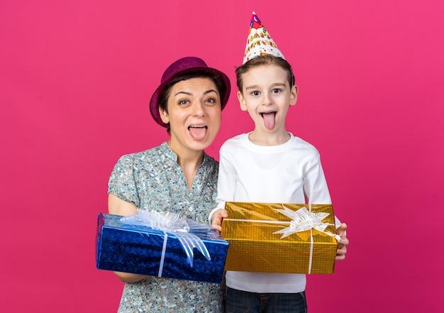 Fröhliche mutter und sohn mit partyhüten, die geschenkboxen isoliert auf rosa wand mit kopienraum halten