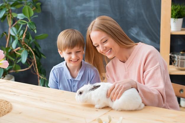 Fröhliche mutter und sohn sitzen am holztisch und spielen mit weißem kaninchen