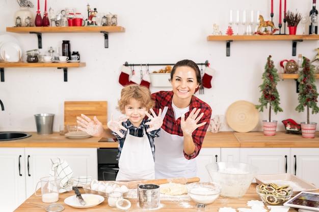 Fröhliche mutter und sohn zeigen ihre hände mit mehl bedeckt, während sie gemeinsam teig in der küche zubereiten