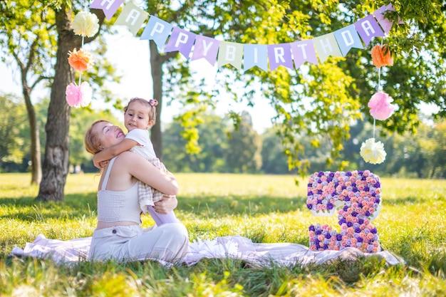 Fröhliche mutter und tochter, die sich am kindergeburtstag auf einer decke mit papierdekorationen im park amüsieren