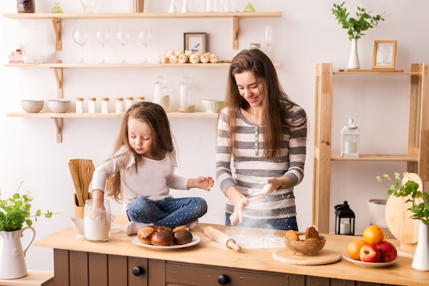 Fröhliche mutter und tochter in der küche bereiten frühstück vor. den teig aus mehl für pfannkuchen, kekse und brötchen kneten. fliegen mehl und alle lachen