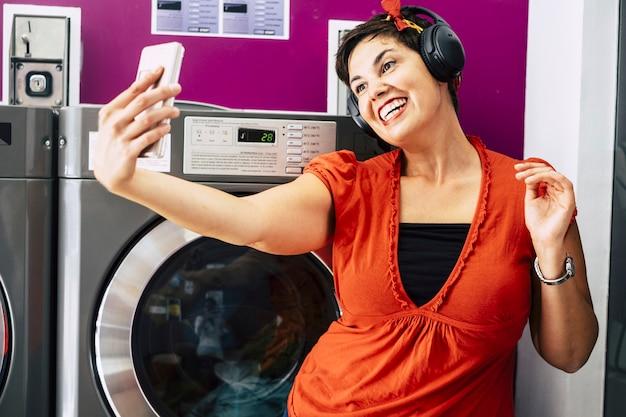 Fröhliche, nette brünette, die im waschsalon ein selfie mit smartphone macht, während sie musik hört und auf ihre kleiderwaschmaschine wartet - junge tausendjährige menschen, die im stadtkonzept leben - wäschereigeschäft