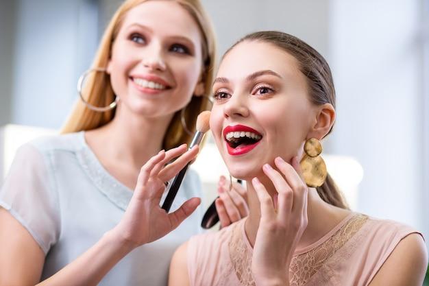 Fröhliche nette frau, die ihre wange berührt, während sie sich über ihr make-up freut
