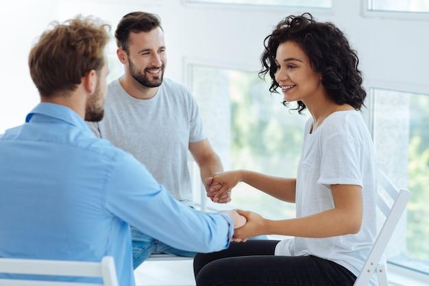 Fröhliche nette positive therapeutin, die hände ihrer patienten hält und lächelt, während sie eine gruppensitzung mit ihnen hat