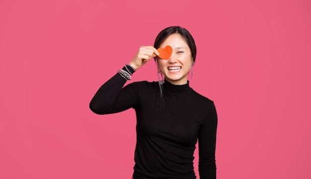 Fröhliche niedliche asiatische toung frau, die über rosa hintergrund steht und rotes papierherz hält
