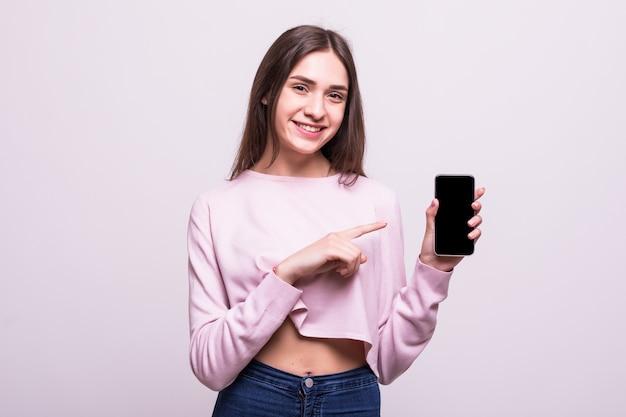 Fröhliche niedliche frau, die finger auf smartphonebildschirm lokalisiert auf einem weißen hintergrund zeigt.