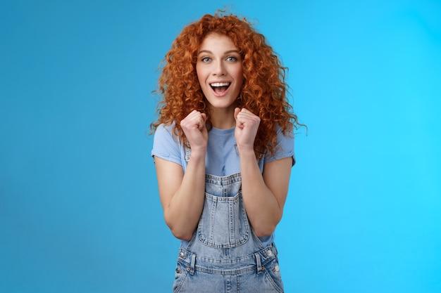 Fröhliche optimistische, glückliche, rothaarige, lockige, attraktive frau, die geballte fäuste jubelt, die freudig lächelt und breit jubelt, indem sie das spiel unterstützen, um motivierten blauen hintergrund aufrechtzuerhalten.