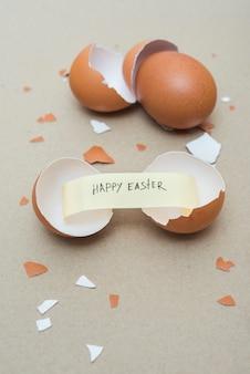 Fröhliche ostern-aufschrift auf kleinem papier im defekten ei