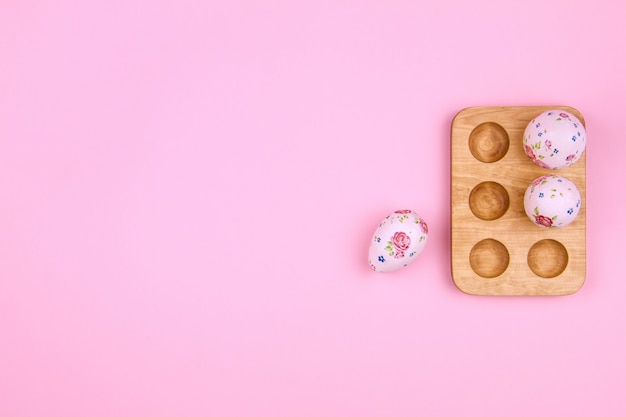 Fröhliche ostern. große und kleine eier tradition ostern mit dem design der blume des frühlinges im hölzernen stand auf rosa hintergrund