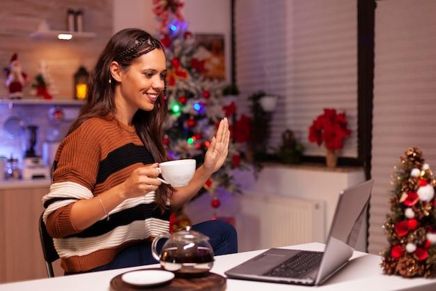 Fröhliche person, die während eines videoanrufs eine tasse tee hält