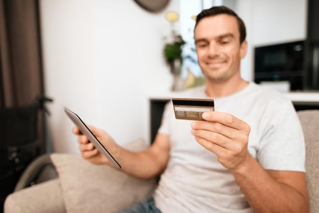Fröhliche person hält kreditkarte und nutzt tablet.