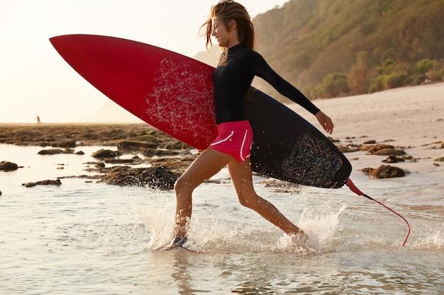 Fröhliche person hat zeit zum surfen, läuft schnell, erreicht die aufstellung, hat einen sportlichen körper