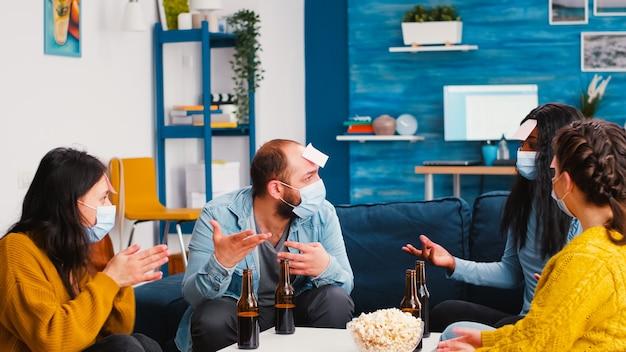 Fröhliche personen mit haftnotizen auf der stirn, die ein namensspiel mit multiethnischen freunden spielen, die aufgrund einer sozialen pandemie sozial distanziert bier im wohnzimmer trinken