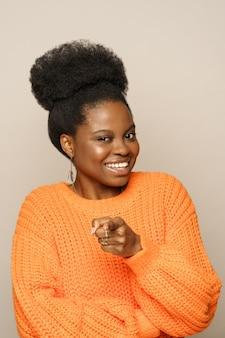 Fröhliche positive afro-frau mit lockigem haar tragen orangefarbenen pullover, der sie zeigt, grauer hintergrund des studios
