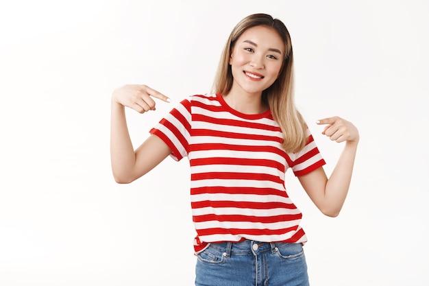 Fröhliche positive gutaussehende blonde asiatische frau, die auf sich selbst zeigt, zeigt mit den zeigefingern auf die persönliche leistung, die breit lächelt, wurde ausgewählt, stolz vorzustellen, weiße wand