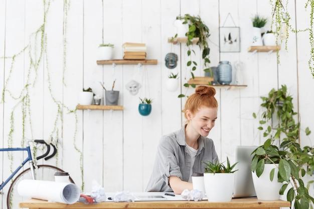 Fröhliche positive junge rothaarige frau designerin mit haarknoten
