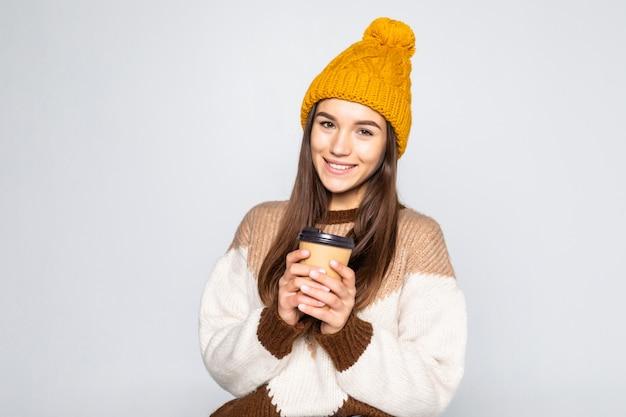 Fröhliche positive koffeinfrau, frau in einem pullover und einem hut mit kaffee in ihren händen, die auf einer weißen wand aufwerfen