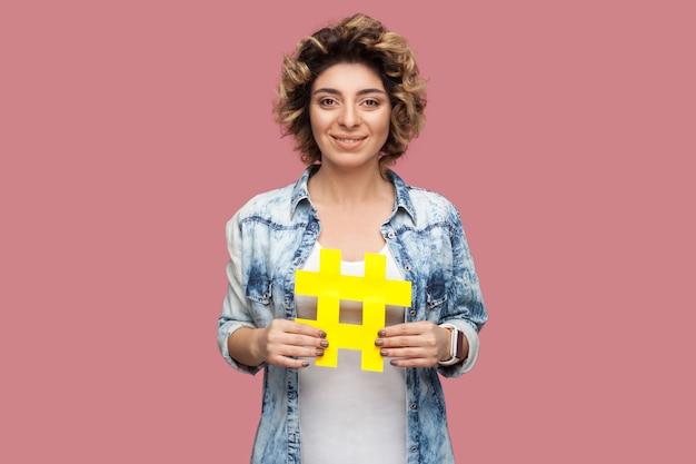 Fröhliche positive optimistische junge frau im blauen hemd mit lockiger frisur, die ein großes großes gelbes hashtag-zeichen hält, social-media-konzept. innen, isoliert, studioaufnahme, kopienraum, rosa hintergrund