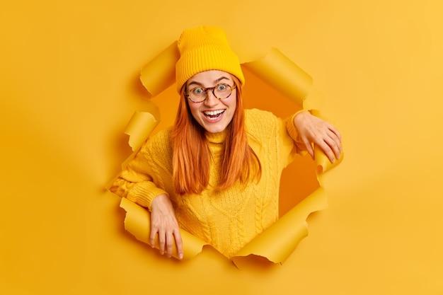 Fröhliche positive rothaarige frau sieht mit fröhlichem ausdruck aus, hat gute laune, trägt gelben hut und pullover und freut sich, durch zerrissenes papier für ein foto zu posieren
