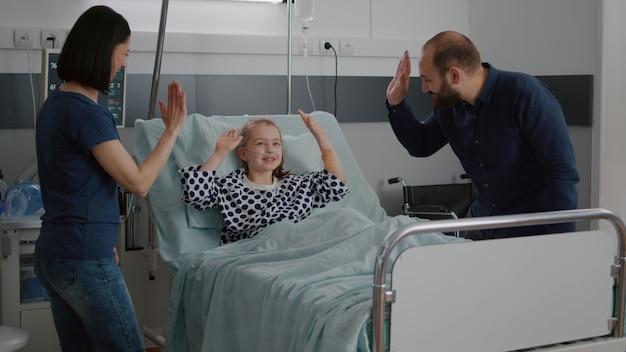 Fröhliche positivität-familie, die während der genesungsuntersuchung high five mit der kleinen tochterpatientin teilt