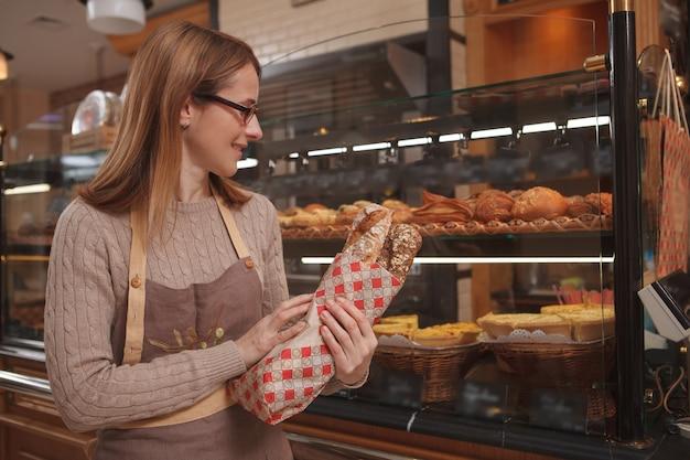 Fröhliche professionelle bäckerin, die frisches leckeres brot hält und in ihrer bäckerei arbeitet