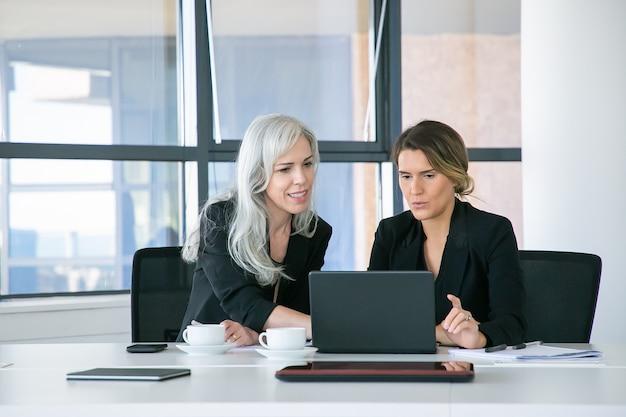 Fröhliche projektmanager, die laptopanzeige beim sitzen am tisch mit tassen kaffee und papieren im büro betrachten. vorderansicht. teamwork und kommunikationskonzept