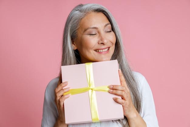 Fröhliche reife asiatische dame hält geschenkbox mit band posiert auf rosa hintergrund