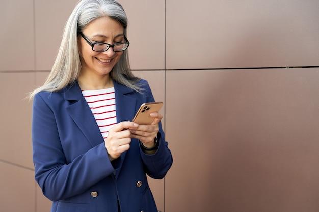 Fröhliche reife dame in geschäftskleidung überprüft ihre telefon-updates