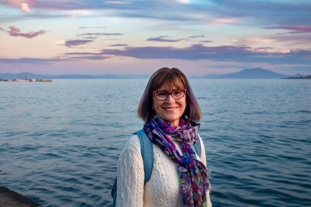 Fröhliche reife frau mit brille, die weißen pullover und bunten schal trägt, der nahe dem meer hinter ihr in griechenland lächelt. glücks- und urlaubskonzept.