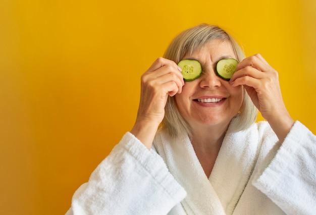 Fröhliche reife frau mit scheiben von gurkenkeilen, die ihre augen vor einem gelben hintergrund bedecken. spa-schönheitsbehandlungen, körperpflegekonzept, bio-kosmetik. natürliche spa-behandlung. platz für text