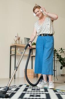 Fröhliche reife hausfrau in freizeitkleidung, die musik in kopfhörern hört, während teppich im wohnzimmer mit staubsauger gereinigt wird