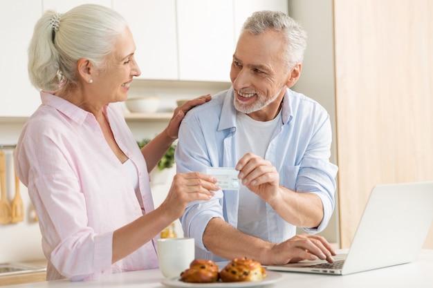 Fröhliche reife liebespaarfamilie mit laptop, die kreditkarte hält