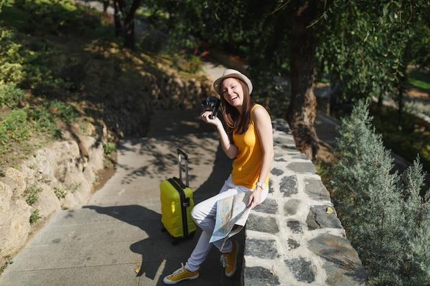Fröhliche reisende touristenfrau in freizeitkleidung, hut mit koffer, stadtplan mit retro-vintage-fotokamera im freien. mädchen, das ins ausland reist, um am wochenende zu reisen. tourismus reise lebensstil.