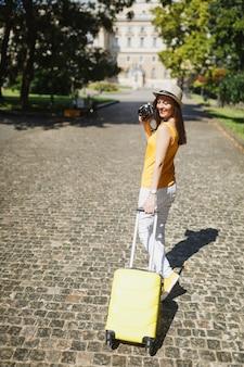 Fröhliche reisende touristenfrau in gelber kleidung mit koffer fotografieren auf retro-vintage-fotokamera, die in der stadt im freien spazieren geht. mädchen, das am wochenende ins ausland reist. tourismus reise lebensstil.