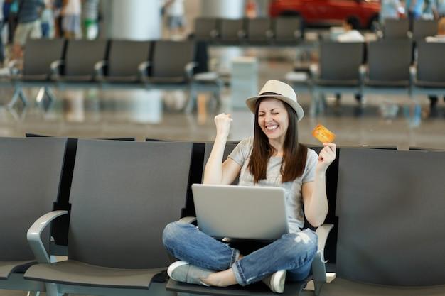 Fröhliche reisende touristenfrau mit laptop, die mit gekreuzten beinen sitzt, siegergeste hält kreditkarte wartet in der lobbyhalle am flughafen?