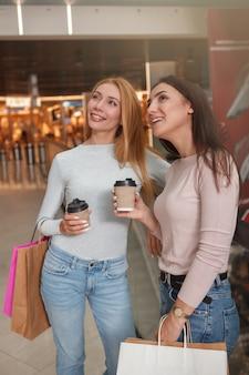 Fröhliche reizende frauen, die kaffee am einkaufszentrum genießen, das saisonalen verkauf genießt