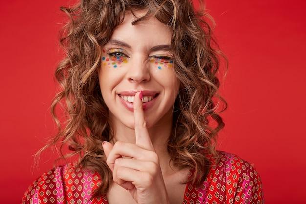 Fröhliche reizende junge frau mit lockigem haar, die festliches make-up trägt, mit breitem glücklichem lächeln zwinkert und zeigefinger auf ihren lippen hält, bittet, geheim zu halten, isoliert